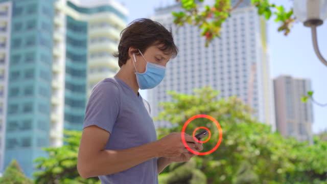 konzept einer kontaktverfolgungs-app zur bewältigung der covid-19-pandemie. der mensch erhält eine benachrichtigung, dass potenziell gefährliche person in der nähe geht. smartphones tauschen daten über soziale kontakte ihrer besitzer aus - smartphone mit corona app stock-videos und b-roll-filmmaterial