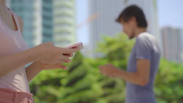 konzept einer kontaktverfolgungs-app zur bewältigung der covid-19-pandemie. coronavirus mobile application - menschen auf einer stadt straße verwenden smartphones mit einer installierten app, um die kontaktverfolgung in reaktion auf die 2019-20 coronavir - smartphone mit corona app stock-videos und b-roll-filmmaterial
