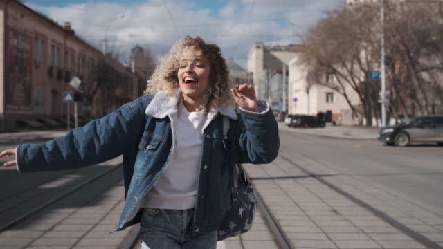 vídeos de stock e filmes b-roll de concept of carefree fun and joy. young girl dancing funny on the street. - mochila saco