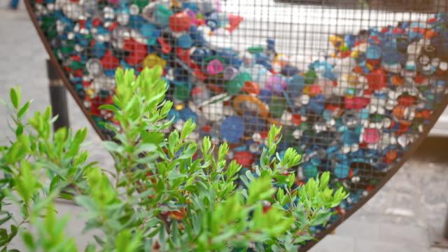 koncept för uppsamling av plastavfall och sopor i städer. grön växt buske och hjärtformade järn bur för att samla sällskapsdjur omslag och flaskor. begreppet naturvård, miljöförorening - recycling heart bildbanksvideor och videomaterial från bakom kulisserna