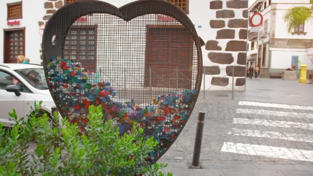 teneriffa, kanarieöarna, spanien-januari, 2019: begreppet insamling av plastavfall och sopor i städer. grön växt buske och hjärtformad järnbur för att samla sällskapsdjur omslag och flaskor - recycling heart bildbanksvideor och videomaterial från bakom kulisserna