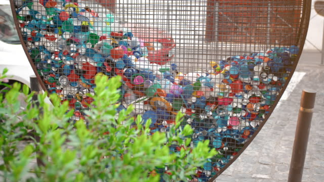 concept of collecting plastic waste and garbage in cities. green plant bush and heart-shaped iron cage for collecting pet covers and bottles. concept of nature conservation , environmental pollution - earth day stock videos & royalty-free footage