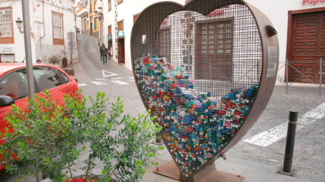 concept of collecting plastic waste and trash on the streets. heart-shaped iron cage for collecting pet covers and bottles. the concept of conservation of nature, environmental pollution - earth day stock videos & royalty-free footage
