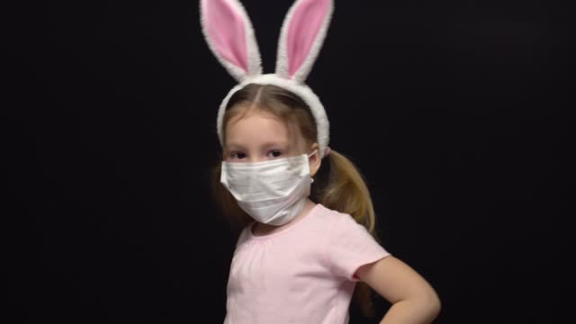 Concept of coronavirus and air pollution. A little girl wears a mask for protection and an Easter Bunny ears costume. Worries about a ruined holiday. Waving the handles and spinning. Meeting of the holiday during the COVID-19 pandemic. Isolated on a black