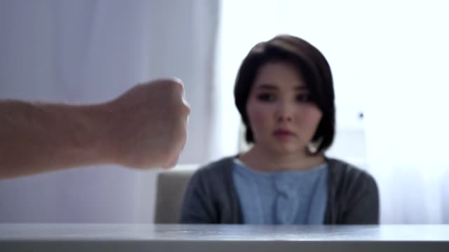 Concept of domestic violence in family, Slams Fist On Table, fearful Asian woman sitting at table in the background 50 fps