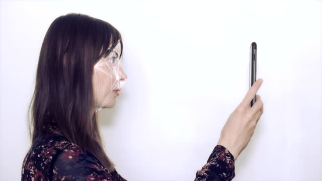 Concept of facial recognition. Woman holding up her mobile device for facial recognition. medical scanner stock videos & royalty-free footage
