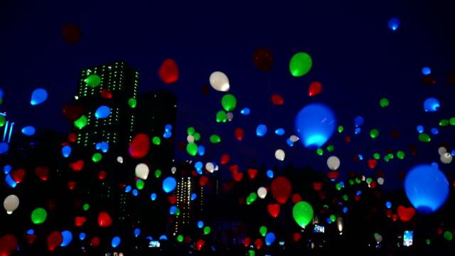 愛の饗宴の概念。夜市の空に飛行色ヘリウム光る風船風船 - 謝肉祭点の映像素材/bロール