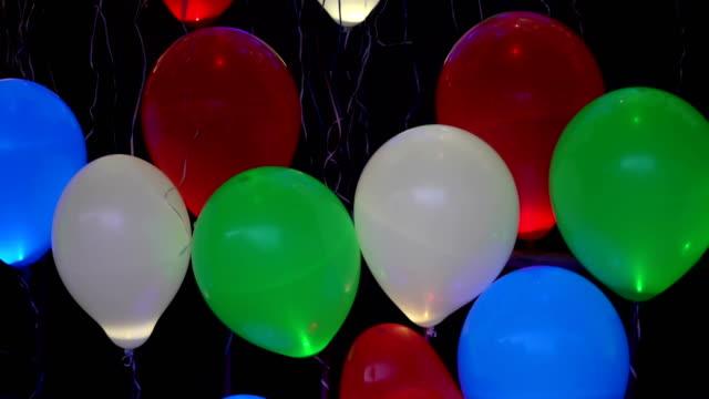 愛の饗宴の概念。黒の背景、バレンタインの日、正月、クリスマス、赤いハートのバルーンの形に最適で発光色ヘリウム光る風船を飛んでください。 - 謝肉祭点の映像素材/bロール