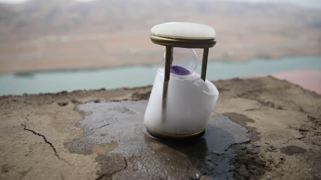 vídeos de stock e filmes b-roll de a concept of frozen time. hourglass in ice. creative artwork decoration. selective focus - climate clock