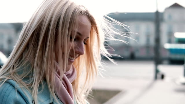 Concept of happy memories. Slow motion. Portrait of happy Caucasian woman side view. Flying blonde hair in counterlight video