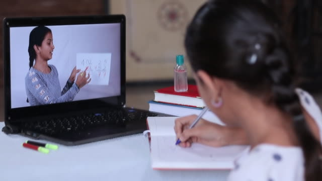 concept of homeschooling or e-learning, young girl busy in writing by looking into laptop while teacher explaining during covid-19 or coronavirus pandemic crisis. - india video stock e b–roll