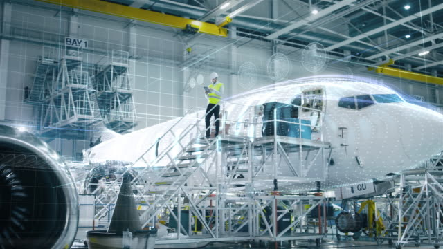 concept of: in hangar engineer holding tablet computer standing on a ramp near airplane conducts digitilized maintenance analysis. animated - kadłub samolotu filmów i materiałów b-roll
