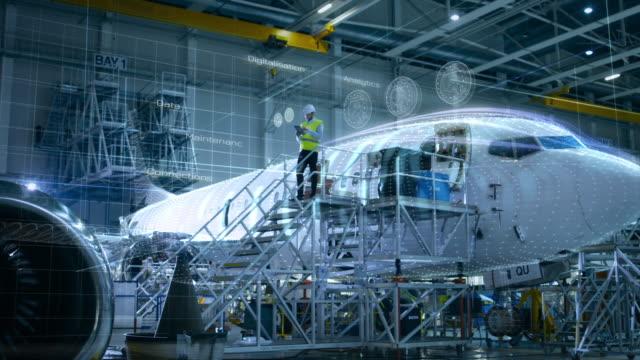 vidéos et rushes de concept de: dans le hangar ingénieur tenant la tablette debout sur une rampe près avion effectue une analyse entretien digitalisés. d'animation - inspecteur