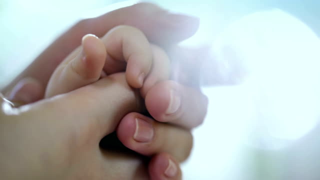 Concept of love and family. hands of mother and baby closeup, Hand in hand. Mother care. Caring mother with baby, Playing with baby. Slow Motion. video