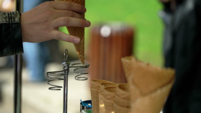 Concept of summer mood. Sale of ice cream in a waffle cup in the city park. Delicacy and hygiene video