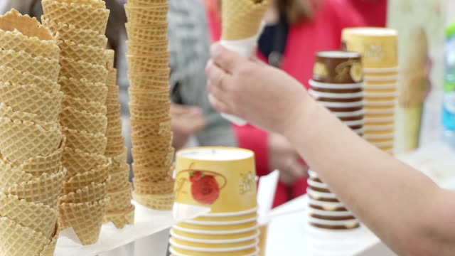 Concept of summer mood. Sale of ice cream in a waffle cup on woman hand in the city park slow motion video
