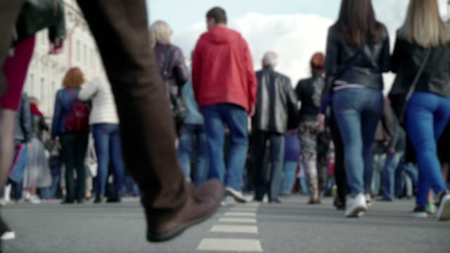 Concept of the crowd unrecognizable people walking on city street. Crowd of people going to or from work or or weekend, holiday in the city with families. Low angle view real time in blur. Concept modern holidays at weekends video