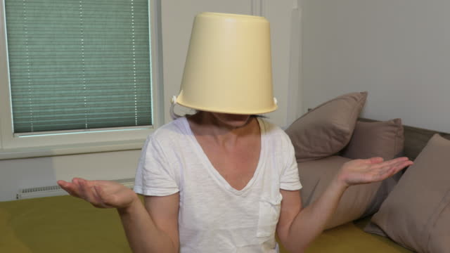 Concept of woman with bucket on head - vídeo
