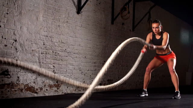 Concept: power, strength, healthy lifestyle, sport. Powerful attractive muscular woman gym trainer do battle workout with ropes at the gym. Slow motion video