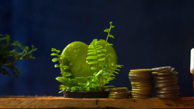 koncept, skandinaviska husmodell och högen av mynt pengar på brun planka, med stormigt. 1080p, 23,976 fps - dept bildbanksvideor och videomaterial från bakom kulisserna