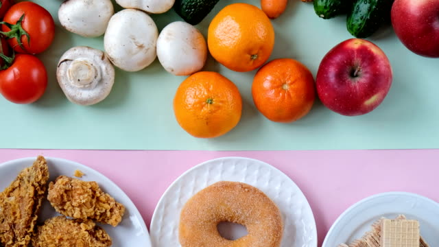 concept shot of healthy and unhealthy food. fruits and vegetables vs fast food. view from above, flat lay - вредное питание стоковые видео и кадры b-roll
