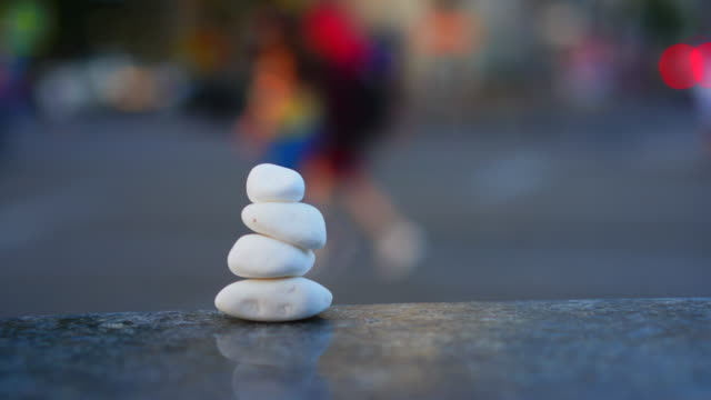 Concept Symbol of calm and meditation on the background of the city bustle and traffic. Stones sea pebbles in the form of a pyramid
