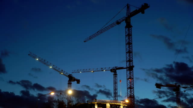 Concept teamwork, crane as symbol new life and changes in night city. Spotlight light construction video