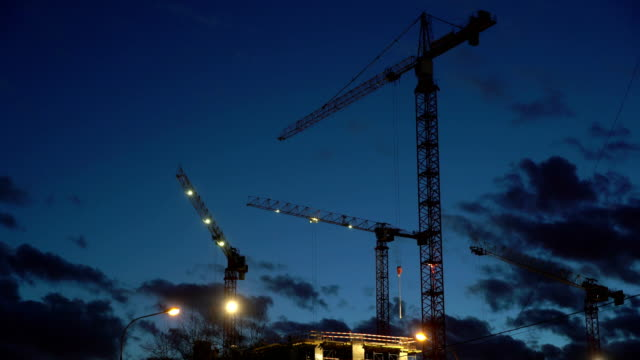 Concept teamwork, crane as symbol new life and changes in night city. Timlapse video