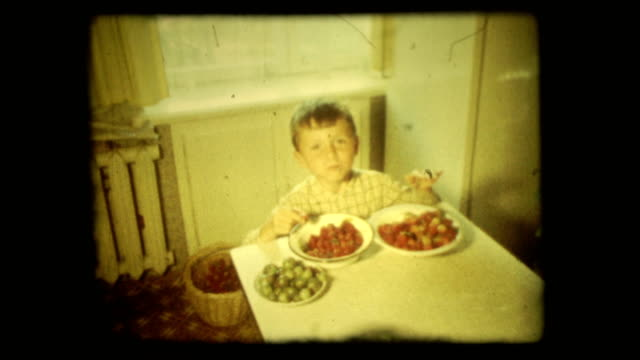 Concept vintage 8 mm film screen with 4 x 3 ratio. Five-year boy eats with pleasure gooseberries