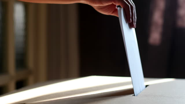 Conceptual footage of a person voting during elections