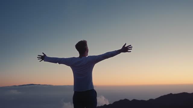 vídeos de stock, filmes e b-roll de vídeo conceitual do vencedor. um homem levanta suas mãos para cima, de pé no topo de uma montanha, acima das nuvens e vento forte a soprar - troféu