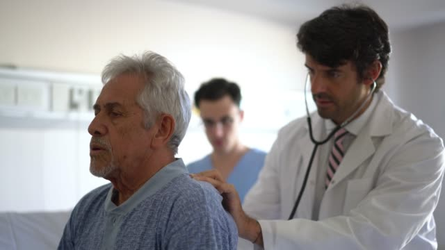 vídeos de stock e filmes b-roll de concerned doctor checking the lungs of his patient with a stethoscope while dictating something to the nurse - exame