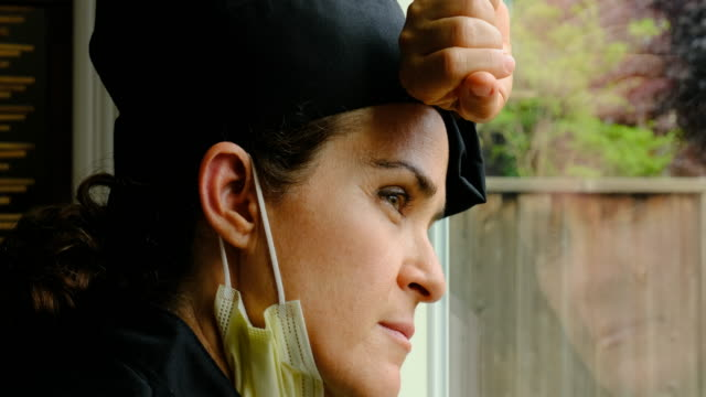 Concerned female chef restaurant owner because her business is down because Covid-19 Concerned caucasian female chef restaurant owner because her business is down because Covid-19 looking away through a window bankruptcy stock videos & royalty-free footage
