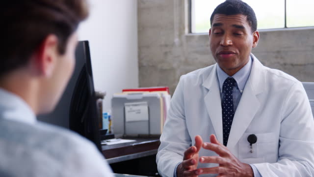 Concerned mixed race male doctor speaking to patient