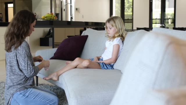 Concerned Mother Applying Adhesive Bandage to Daughter