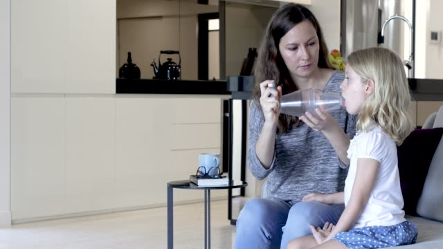 Concerned Mother Giving Asthma Treatment To Asthmatic Daughter video