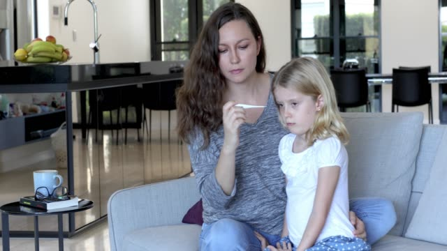 Concerned Mother Taking Child's Temperature With Thermometer