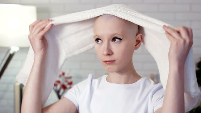 bir başörtüsü koyarak kemoterapi ilgili kadın - meme hayvan vücudu bölümleri stok videoları ve detay görüntü çekimi