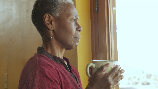 Concerned worried black woman holding a hot coffee cup looking out a window