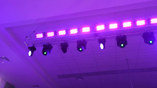 Concert lighting equipment in work. Professional lighting projectors automatically rotated and shining of different colors. Rays from the light equipment get into the camera lens video
