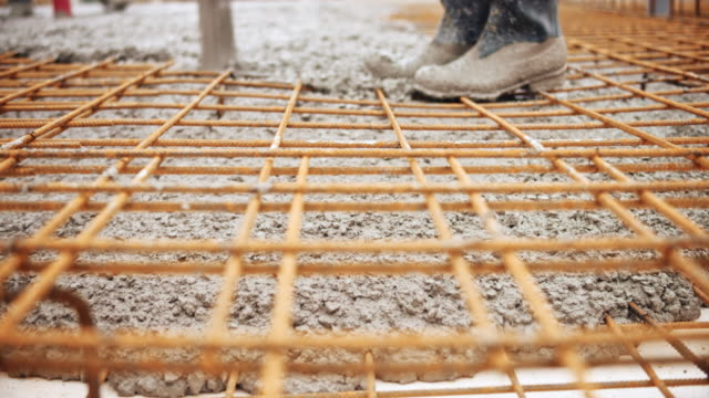 Concrete being poured and flowing below the concrete wire mesh Medium low angle handheld shot of concrete flowing below the wire mesh as it is being poured onto the steel reinforcement. Shot in Slovenia. prop stock videos & royalty-free footage