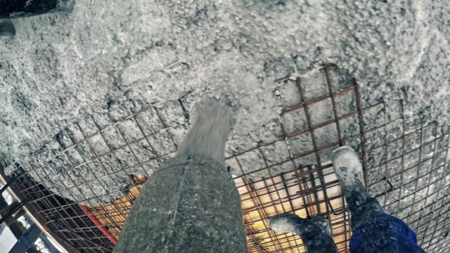 pov concrete being poured onto the steel reinforcement - spranga video stock e b–roll