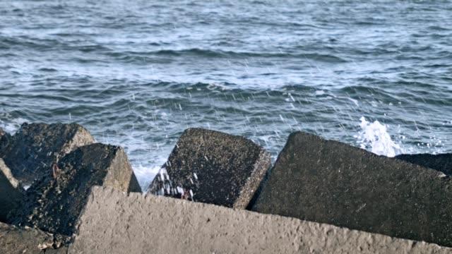 Concrete breakwaters. Water splash on pier rock. Sea waves crashing on rock video