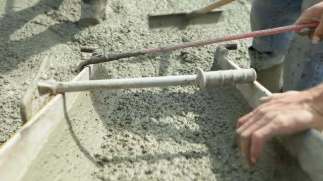 Beton fließt von Mischpult durch den Arbeitnehmer und Leveling – Video