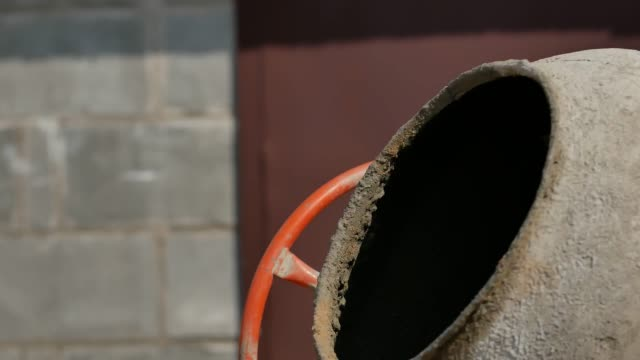concrete is mixed in a concrete mixer close-up