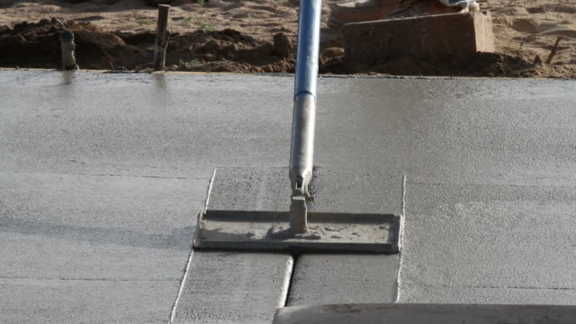 Concrete lines being cut into pour A fresh concrete pour can be seen and a man cutting lines into it block shape stock videos & royalty-free footage