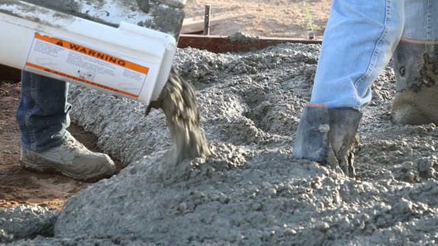 Concrete patio Concrete can be seen pouring out. Two male workers can be seen moving the concrete around inside a form. solid stock videos & royalty-free footage