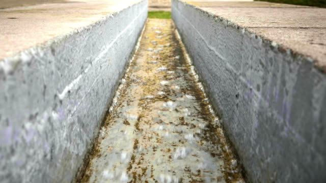 Concrete trough with flowing water, modern water fountain, park architecture video