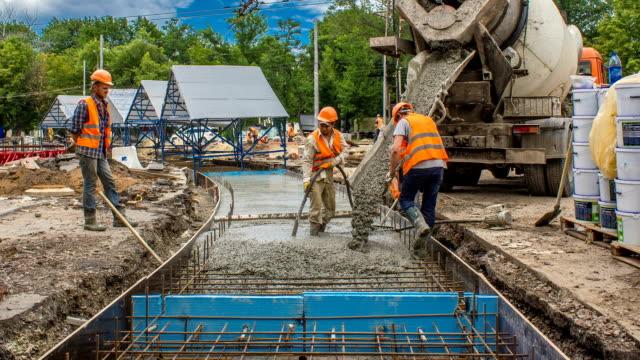 コンクリートの作業の多くの労働者とミキサー タイムラプス道路建設のため - 錆びている点の映像素材/bロール