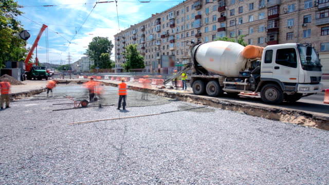 Concrete works for road maintenance construction with many workers and mixer timelapse Concrete works for road maintenance construction with many workers and mixer timelapse. Reconstruction of tram tracks foundation make up stock videos & royalty-free footage